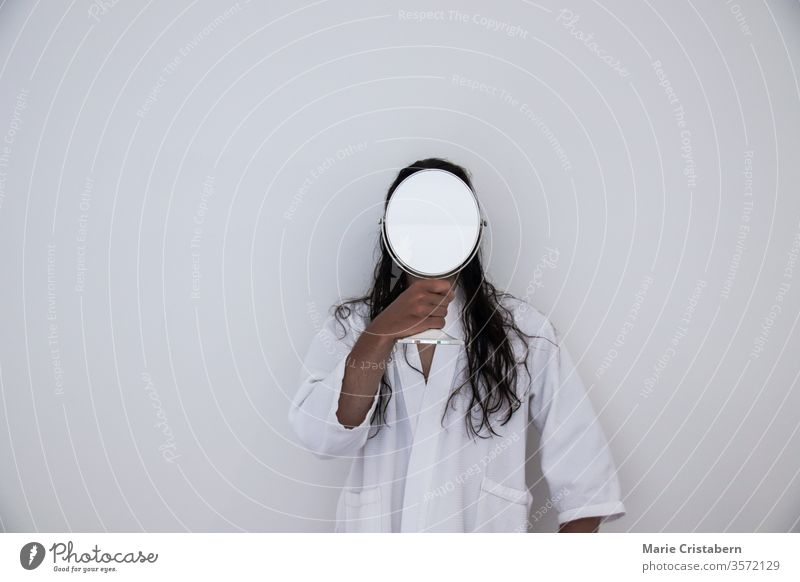 Conceptual photo of a long haired man in white robe holding a mirror in front of his face conceptual image identity concept anonymity mysteriousness