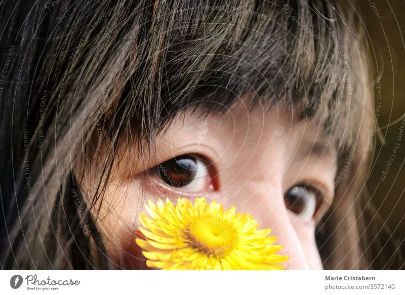 Close up of a yellow flower on the face of an almond eyed asian girl innocence pureness childhood portrait happy Portrait photograph Colour photo expression