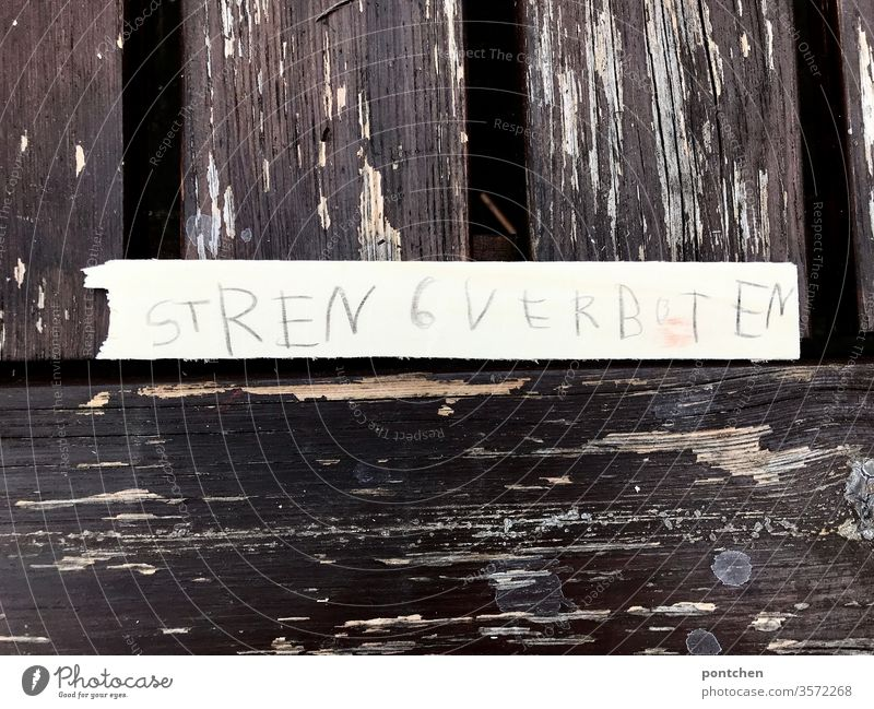 The words strictly forbidden are written in children's handwriting on a strip of paper lying on an old wooden table where the varnish is chipping off Education, pedagogy, strict
