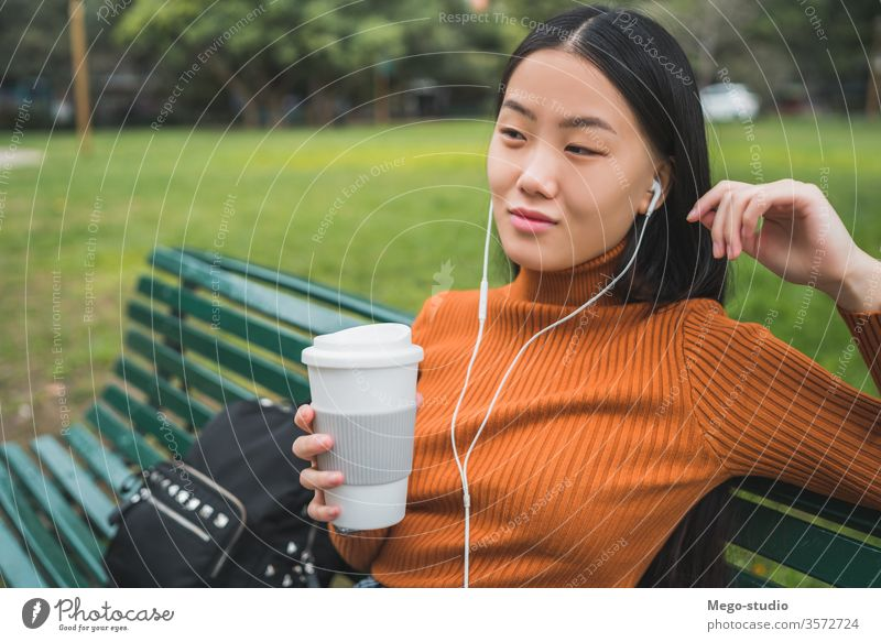 Asian woman listening to music. coffee girl asian park outdoor young beautiful headphones person outside lifestyle chinese female city green people japanese