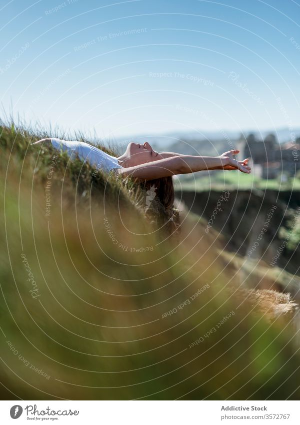 Dreamy woman lying on grass in mountains dreamy relax enjoy vacation travel tranquil summer female cantabria spain meadow sunny nature eyes closed idyllic