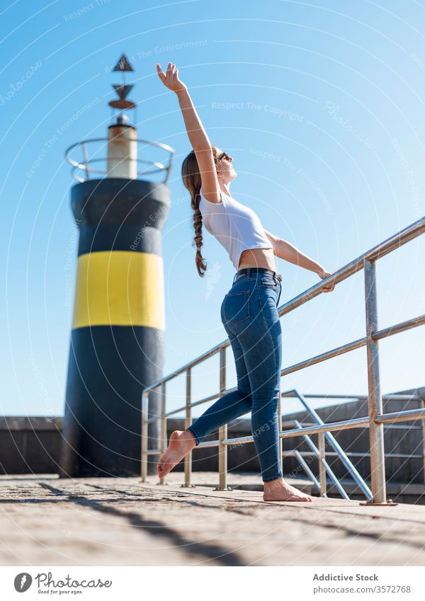 Content woman with raised arm at waterfront content dreamy embankment lighthouse enjoy seafront relax summer travel female cantabria spain casual barefoot stone