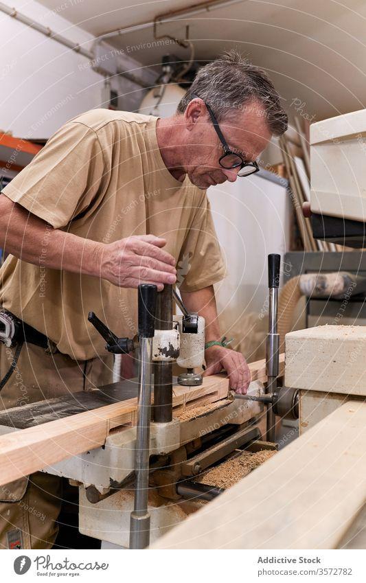 Diligent carpenter drilling timber in modern workroom carpentry woodwork processing handcraft man workshop workplace equipment joiner lumber plank craftsman