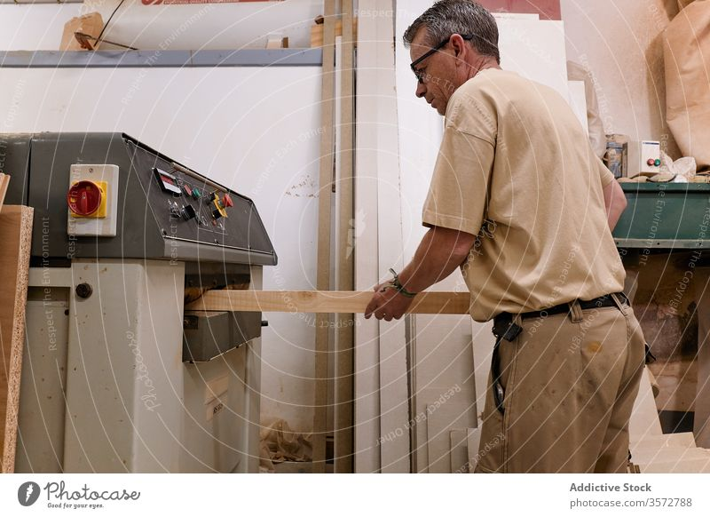 Careful pensive woodworker planing wood beam using machine in contemporary workshop master lumber grind carpenter processing man control artisan plane panel