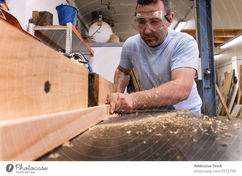 Skilled woodworker using milling machine while working with lumber in contemporary workroom carpenter glasses workshop sawdust safety man detail control timber