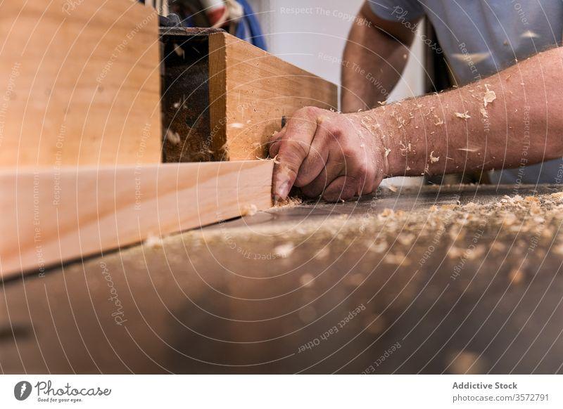 Craftsman milling lumber using machine in carpentry workroom sawdust hand timber craftsman woodwork joiner precise master design carpenter male workshop