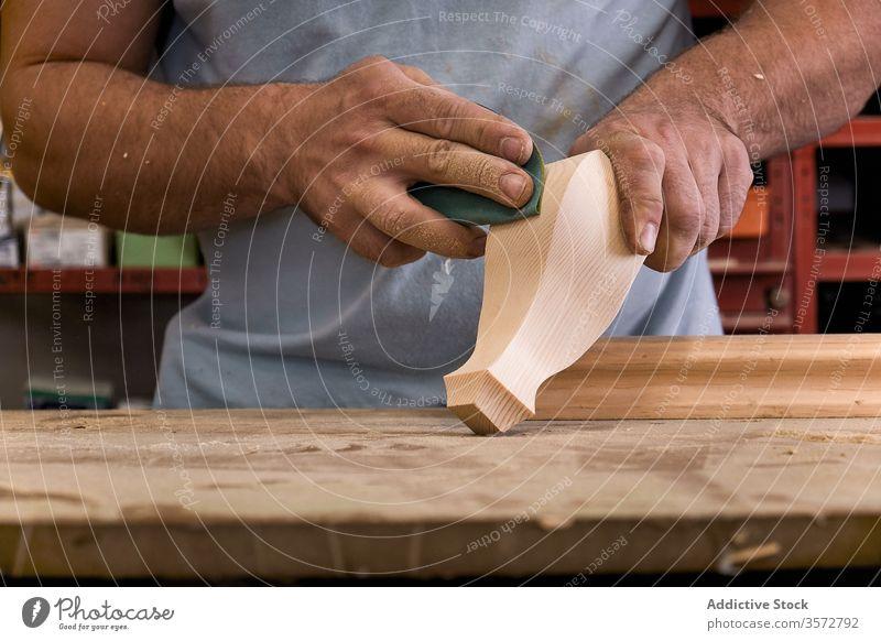 Artisan polishing wooden detail using sandpaper in carpentry workshop artisan control woodwork hand master man tool handwork craftsman workroom handicraft