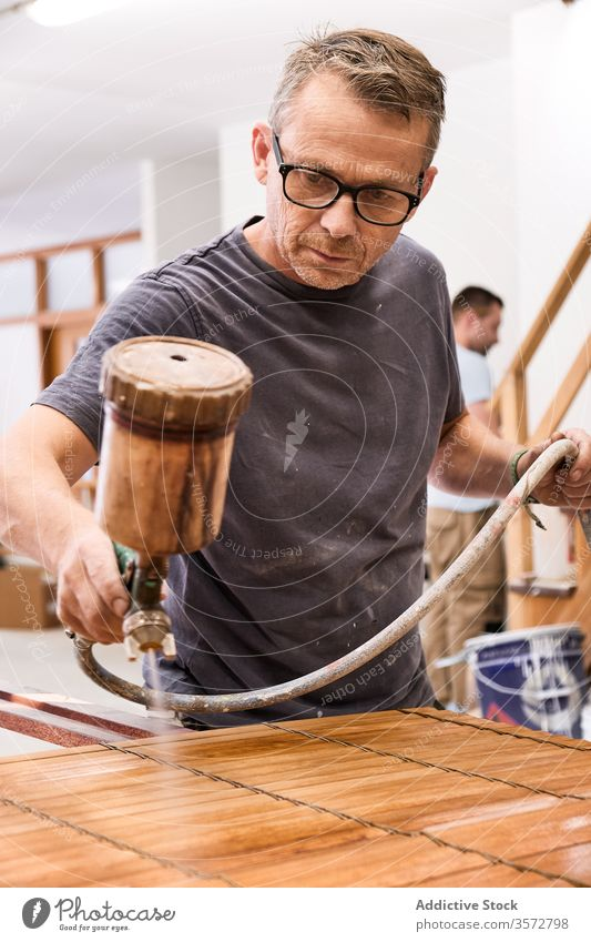 Craftsman applying varnish to wood jalousie using airbrush in carpentry workshop craftsman spray lacquer slats woodwork sprayer tool spray gun wooden airless