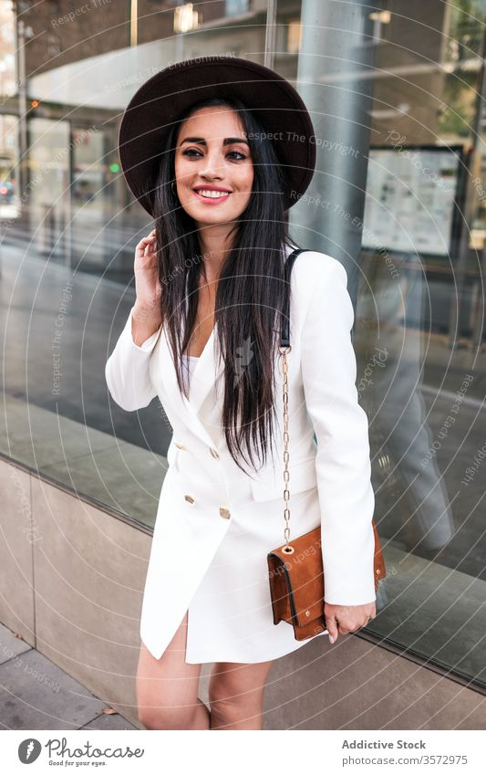 Fashionable young woman standing on city street style trendy fashion spring hat handbag season coat female positive modern confident building glass urban outfit