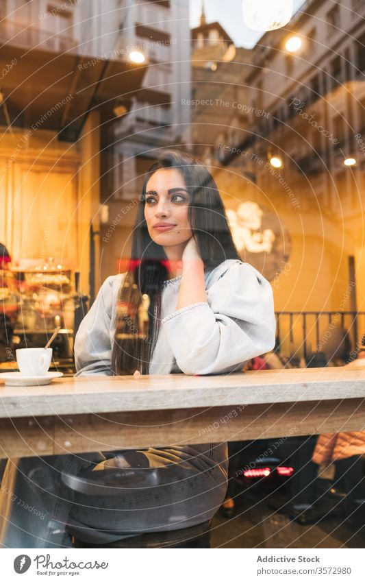Cheerful young woman sitting in cafe cheerful trendy style enjoy coffee window female counter drink cozy cafeteria relax happy lifestyle city rest smile break