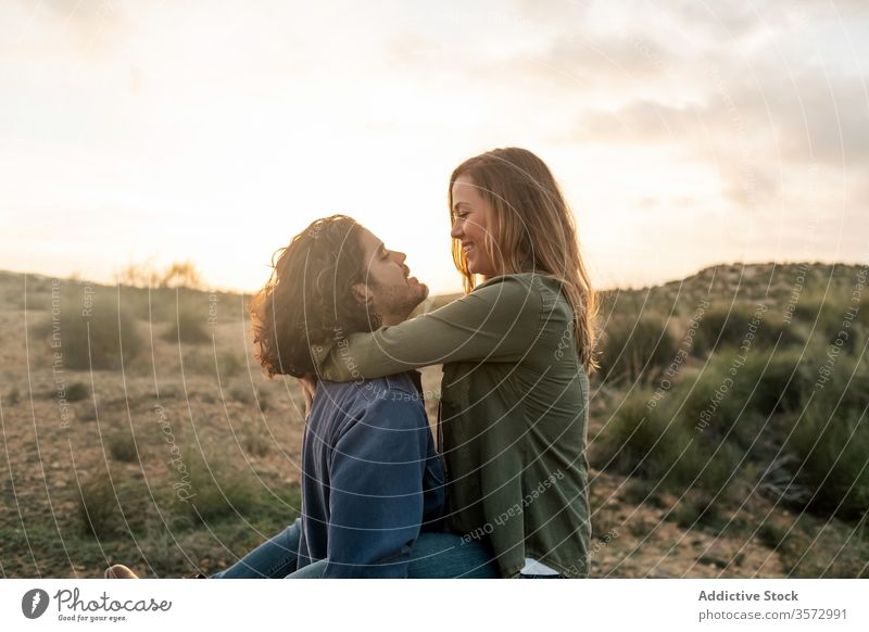 Delighted couple hugging during sunset in nature fun date love together relationship happy man woman romantic cheerful affection lift carry girlfriend boyfriend