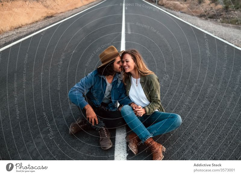 Happy couple sitting on road and touching noses smile touch nose date love countryside travel tender together man woman flirt cheerful casual happy relationship