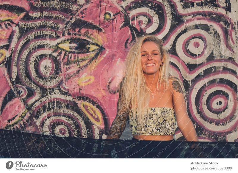Cheerful young lady standing near wall with colorful graffiti on street woman street style freedom happy summer smile art cheerful urban tattoo positive vivid