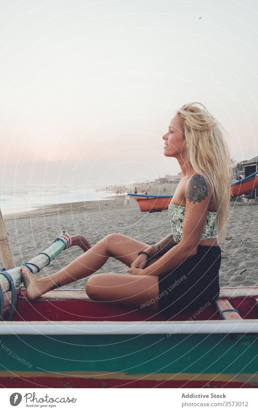 Cheerful lady resting on wooden boat on sandy beach woman ocean coast sunset shore calm harmony solitude peace water bench positive young casual dress summer