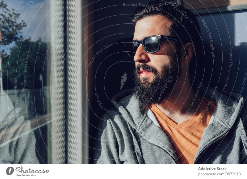 Thoughtful young bearded man looking through window while traveling by train trip dream pensive sunlight summer serious transport passenger seat alone