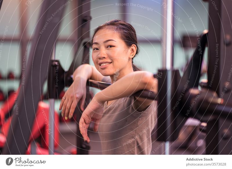 Positive Asian sportswoman leaning on barbell in modern gym and looking at camera rest workout machine content relax proud confident ethnic asian break fitness