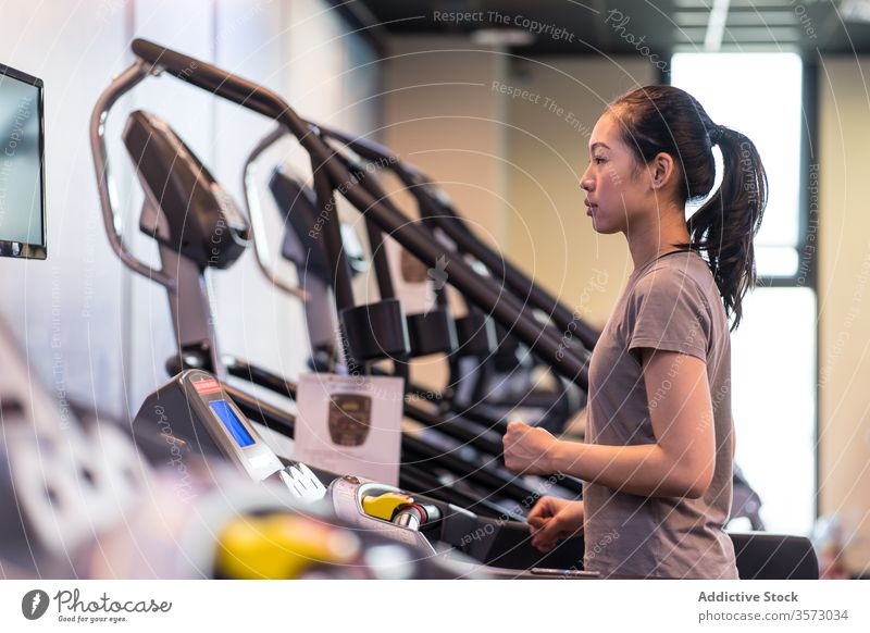 Young ethnic sportswoman running on treadmill while training in modern gym cardio exercise athlete healthy workout fitness slim young active wear wellness