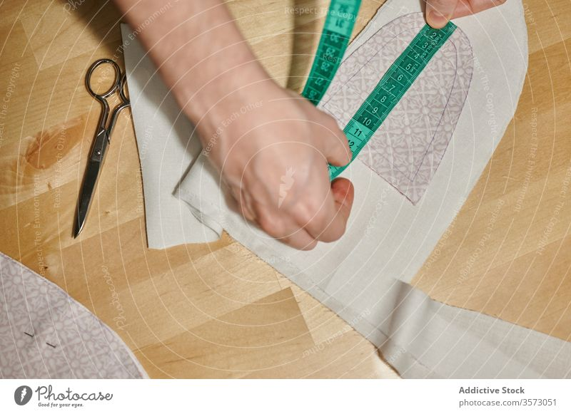 Unrecognizable designer measuring textile detail with tape piece fabric measure material pattern sew scissors wooden table home cloth craft cut process