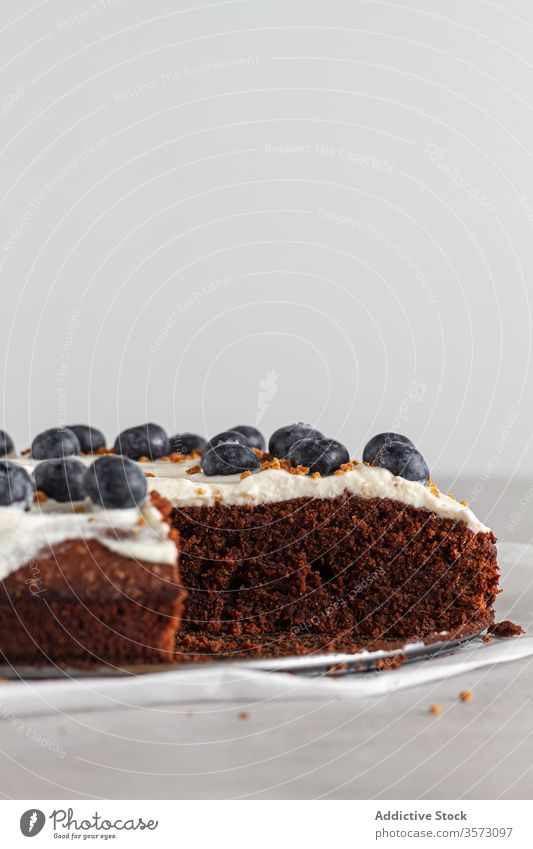 Piece of fresh chocolate cake decorated with blueberries and cream on table in kitchen piece whipped slice sponge biscuit white blueberry food dessert sweet
