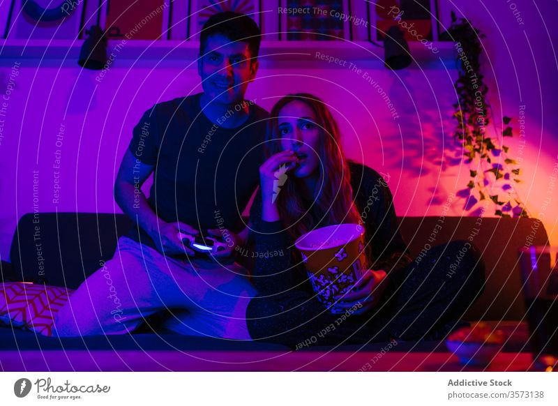 Couple playing game pad and eating popcorn on sofa couple gamepad night fun late together enjoy entertain home sleepless gamer watch thrill using gadget device
