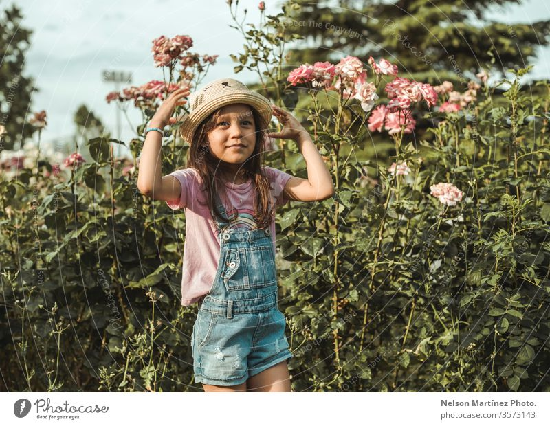 Little girl wearing a cute hat, playing in the park in the summer. little girl child happy grass childhood together nature kids joy people smiling outdoors fun