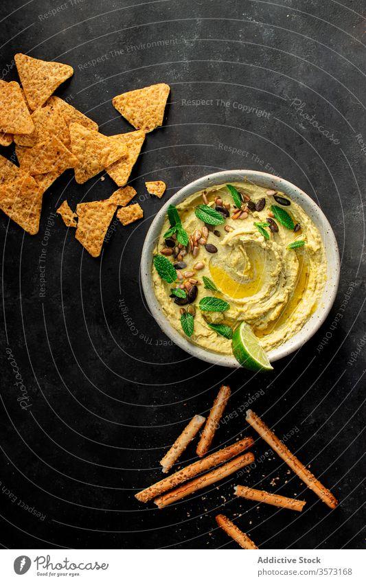 Hummus peas placed on a bowl near crackers antipasto chickpea oil puree health mint lebanese arab dipping antipasti organic tasty veggies middle eastern humus