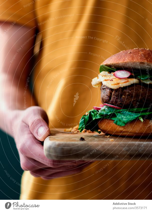 Anonymous person holding delicious vegan lentils burger gourmet hands lentil burger veggie burger fast food eating baked natural lifestyle organic spinach