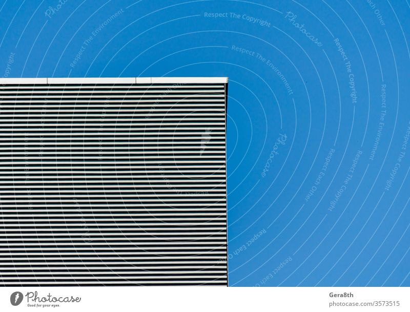 striped wall of a gray tall building against a blue clear sky abstract abstract background angle architecture black blank clean effect empty gelmetry house