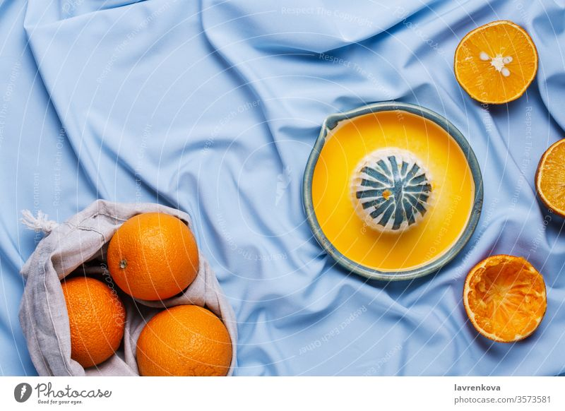 Flatlay of cut oranges and ceramic hand squeeze juicer on blue drapery citrus delicious food fresh fruit healthy ingredient kitchen organic sweet tasty teal
