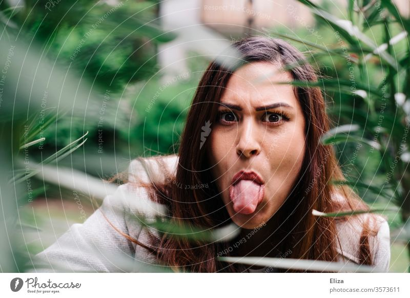 young woman looks evil behind plants in the garden and sticks out her tongue Evil stick out one's tongue Brash Sour Tongue Stick out Adults Human being 1