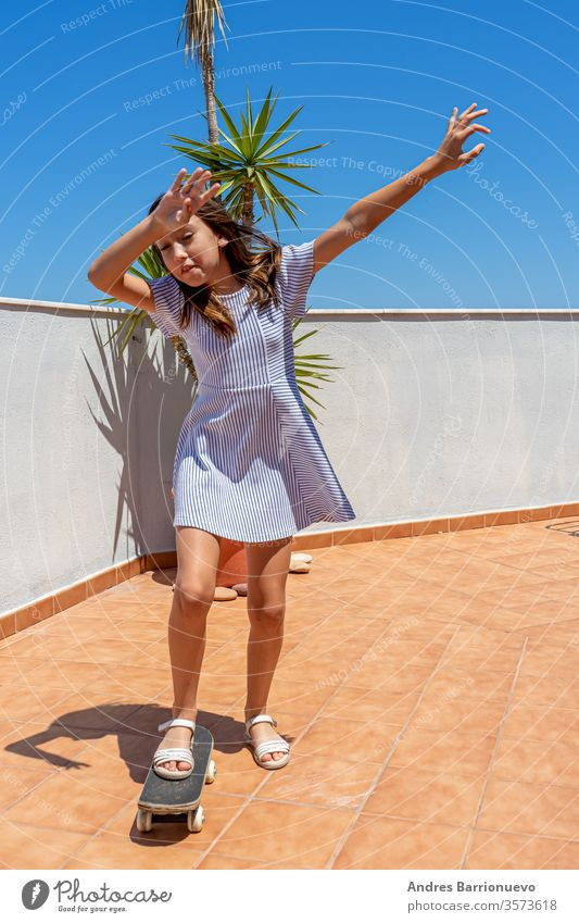 Pretty little girl in a striped dress playing with a skateboard on the terrace of her house look city happy cool clothes summer casual attire stylish fun