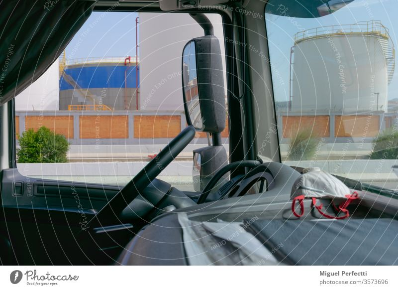 Truck interior, dashboard with a mask and fuel storage tanks in the background truck fuels rearview deposits steering wheel transport vehicle cabin cockpit