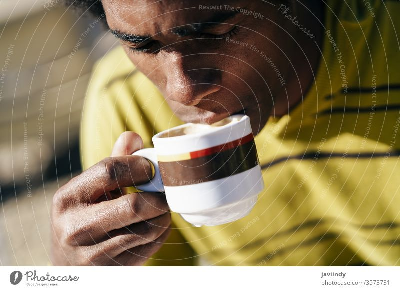 Black man enjoying coffee in cafe while sitting at the table outdoors adult african afro american attractive background beautiful beverage black casual cheerful