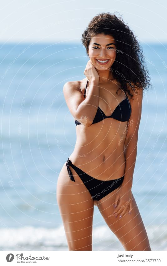 Young arabic woman with beautiful body in swimwear smiling on a tropical beach. bikini summer smile toothy vacation girl travel sea swimsuit happy holiday young