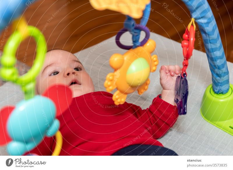 Adorable 6 months old little baby boy on his back surrounded by colourful toys curiosity play enjoyment toddler cute facial expression 6-12 european infant