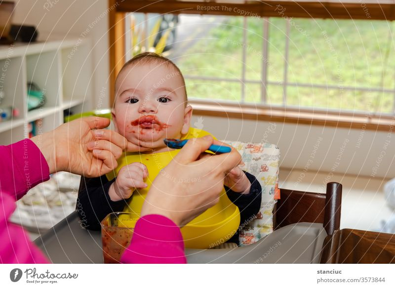 Adorable little baby boy in feeding chair being spoon fed by his mother cute european infant 6 months caucasian educational development adorable expression