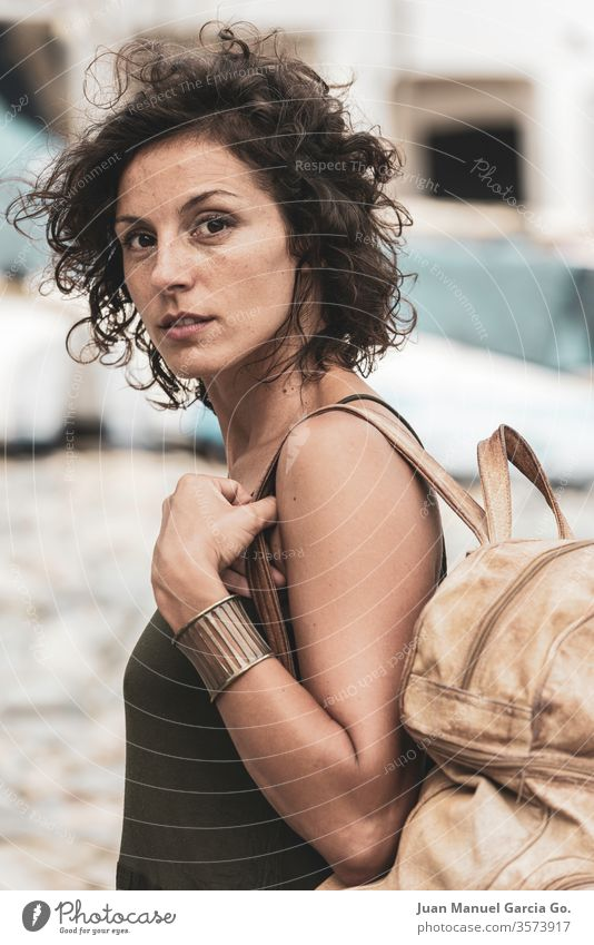 A beautiful female Latina carrying a bag in the shore woman girl beauty young white pretty people attractive adult smiling happy portrait isolated lady natural