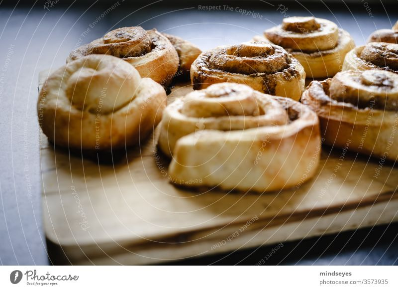 Cinnamon rolls on a wooden board cinnamon buns yeast pastries Food photograph food Colour photo Fresh fragrant Delicious Baking Sweet Baked goods Nutrition