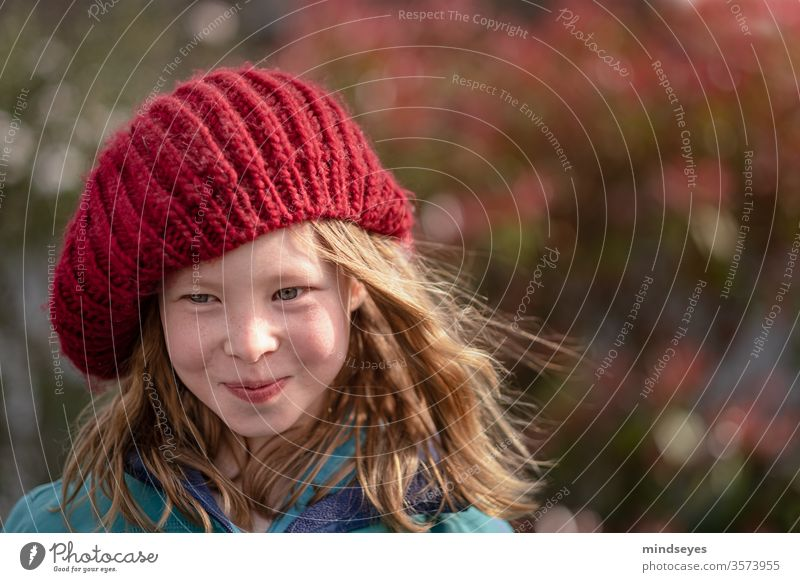 The girl in the cap portrait Winter knitted cap Face Laughter Colour photo Joy long hairs Wind in the hair (if present) Red Knit Headwear smile Humor fun