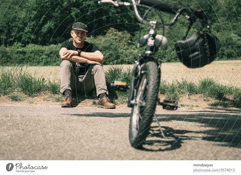 Man sitting behind a child's bicycle in the grass Bicycle Cycling Bike helmet Children's bike Sit Sports Break Nature Exterior shot Leisure and hobbies