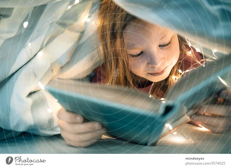 Girl reads book under the covers girl Child portrait Reading Book Bed Duvet Fairy lights Infancy underhand covert thrilling Colour photo Study Interior shot
