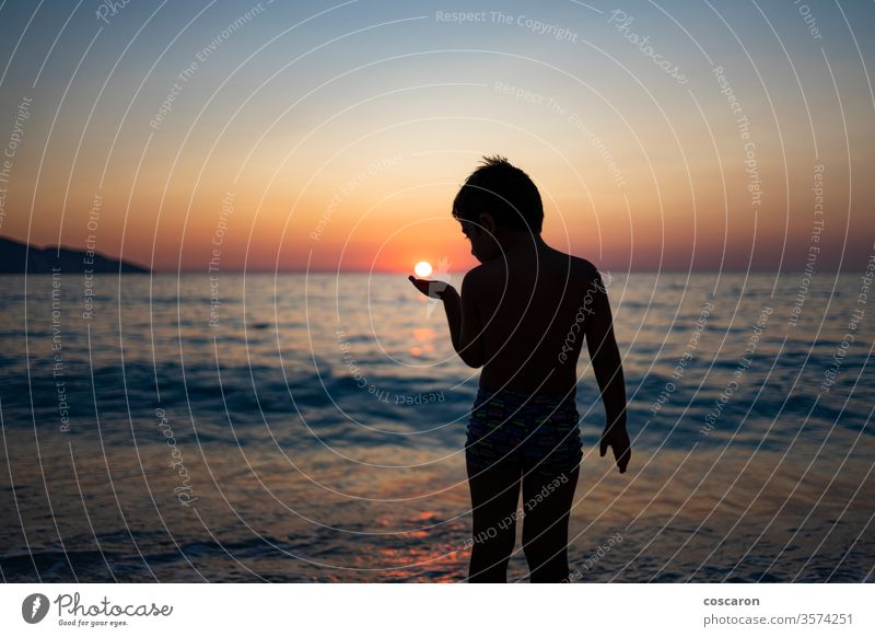 Little kid playing with the sun on the beach at sunset active beautiful boy carefree cheerful child childhood coast coastal evening fun greece hand happiness