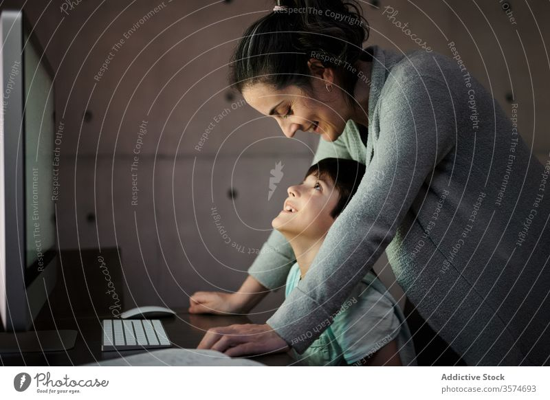 Mother helping kid with homework during online studies mother study education computer explain together child mom schooling son learn knowledge device gadget