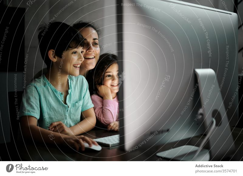 Cheerful woman with kids watching video on computer mother using smartphone together telework childcare happy cheerful home communicate gadget children mom