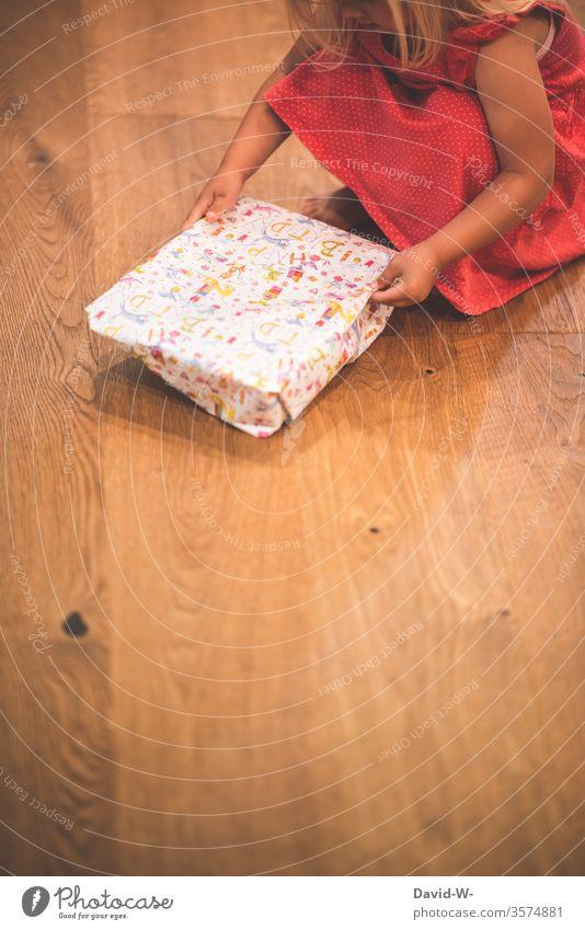 Birthday child unpacks a present Child girl Birthday gift gifts Joy Happy Birthday Donate Ground Parquet floor wooden floor unwrap natural Dress Red