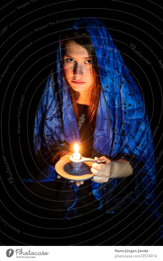 Sad young woman with candle and blue headscarf in front of black background Face Woman sad shoulder stand Headscarf Black portrait Frontal Profile Earnest Art