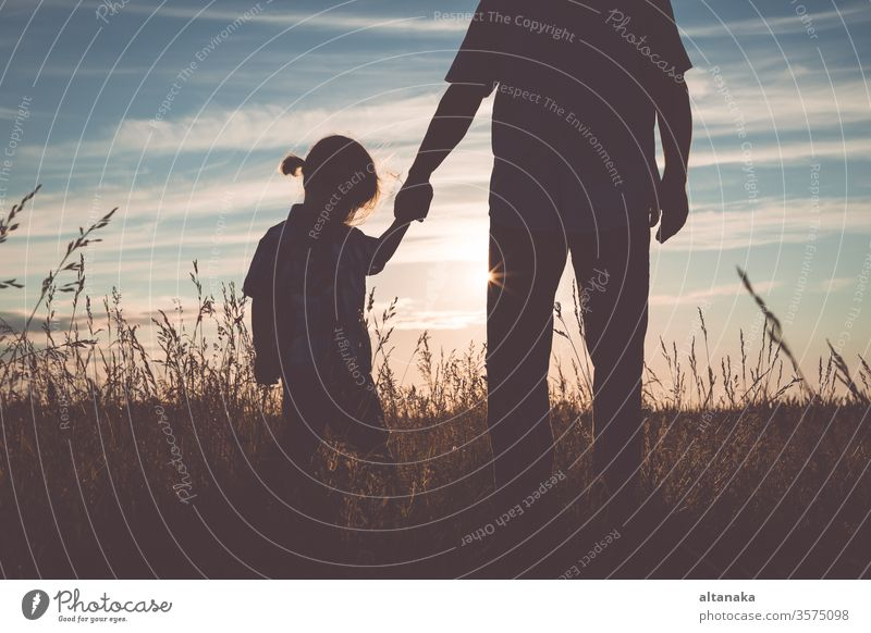 Father and sad son standing in the park at the sunset time. father boy family parent care man people dad child young kid depressed grief unhappy adult together