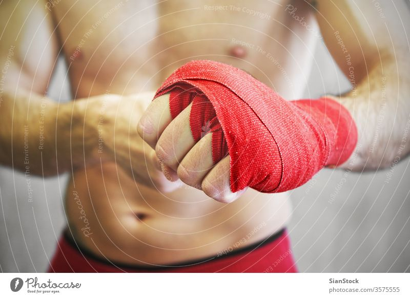 Man is wrapping hands with red boxing wraps. boxer fight man arm background wrist athlete fighter fitness strong muscular isolated sweaty white sports athletic