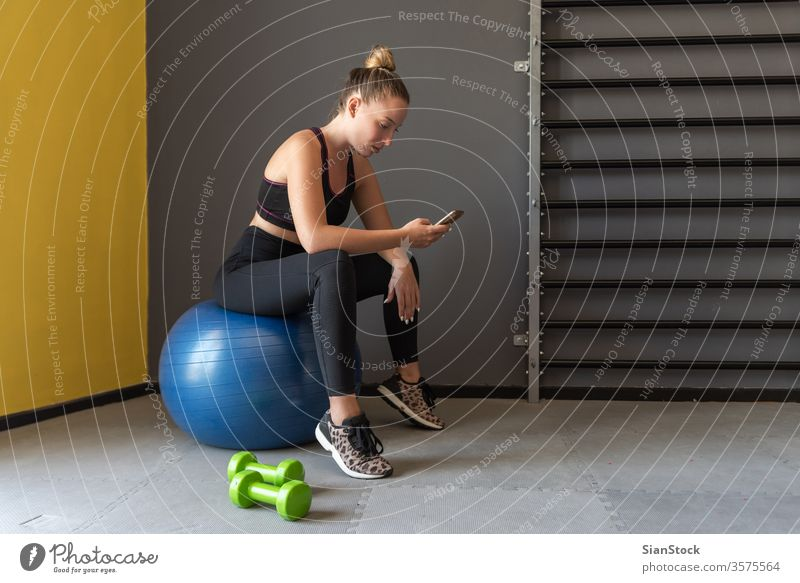 Sport woman sitting, resting and watching her mobile after workout or exercise in fitness gym. app phone sportive slim break dumbbells strength muscular strong