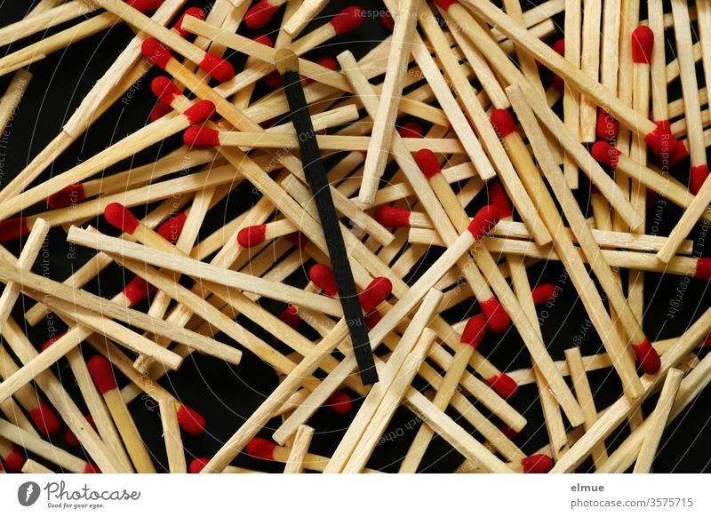 Photochallenge I many matches with red heads and one black match with yellow head on black background Match match head Individualist disorder Heap be different